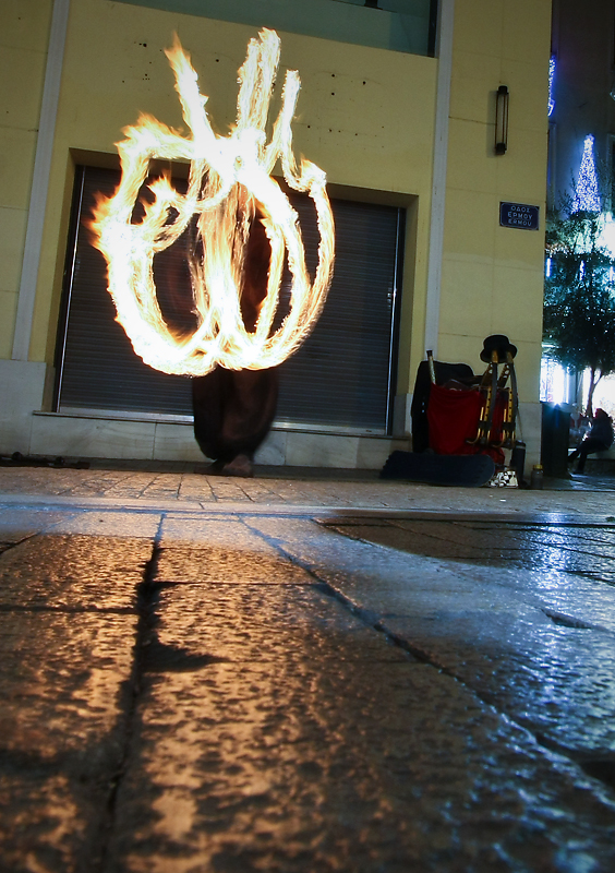 Street artist juggles with torches, Athens, Greece